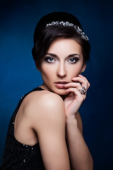 Retrato da mulher moreno bonita no vestido preto sombras cosméticas.