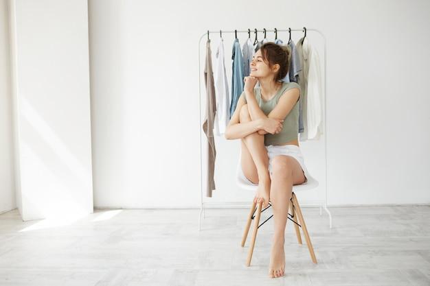 Retrato da mulher moreno nova que sorri olhando no lado que senta-se na cadeira sobre o vestuário do gancho e a parede branca.