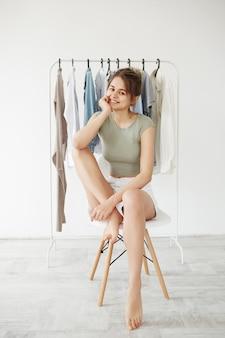 Retrato da mulher moreno nova que sorri sentado na cadeira sobre o vestuário do gancho e a parede branca.