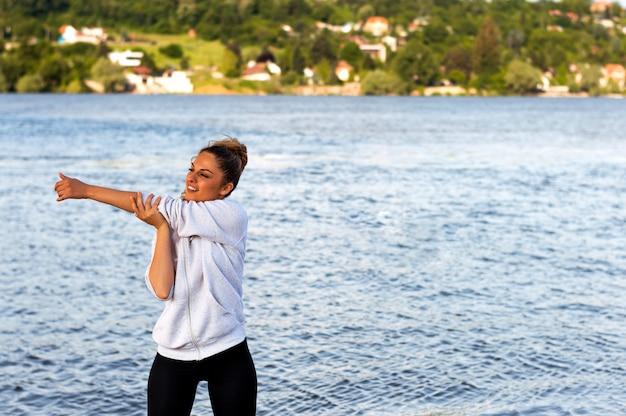 Retrato da mulher nova de sorriso do atleta que prepara-se para um exercício fora perto do rio.