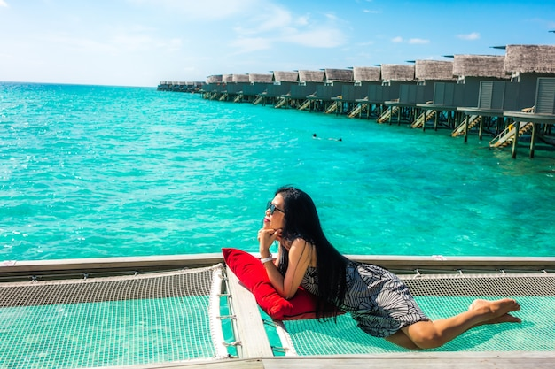 Retrato da mulher nova feliz na casa de campo bonita da água na ilha de maldives. viagens e férias. tiro ao ar livre