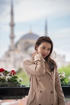 Retrato da mulher que relaxa em istambul perto da mesquita islâmica famosa do marco de hagia sophia.