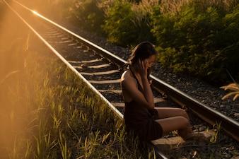 Retrato da mulher que senta-se em uma estrada de ferro nos raios do por do sol.