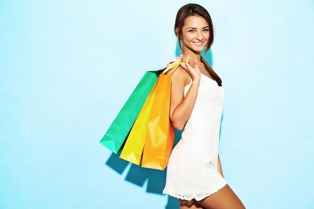 Retrato da mulher shopaholic de sorriso bonita que guarda sacos de papel coloridos. mulher morena posando na parede azul depois das compras. modelo positivo