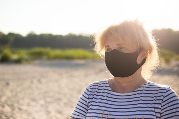 Retrato da mulher superior que veste a máscara médica na natureza na praia, conceito do coronavirus. proteção respiratória