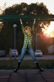 Retrato da noite ruiva ruiva sorridente garota weared em camisa xadrez e macacão jeans, pendurado no chão de esporte ao ar livre