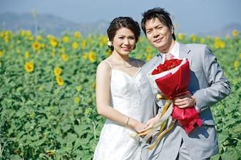 Retrato da noiva e do noivo no campo de girassol