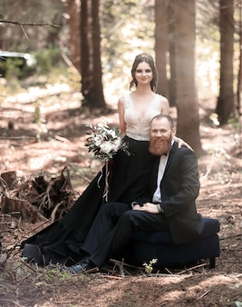 Retrato da noiva e do noivo no fundo de uma floresta de pinheiros