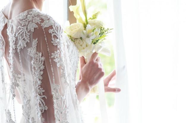 Retrato da noiva linda segurando o buquê perto da janela dentro de casa