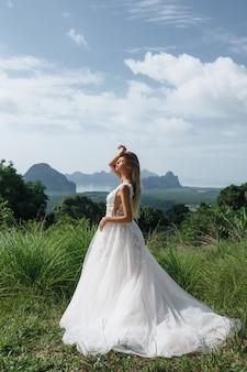 Retrato da noiva loira linda em um vestido de noiva ao ar livre no verão.