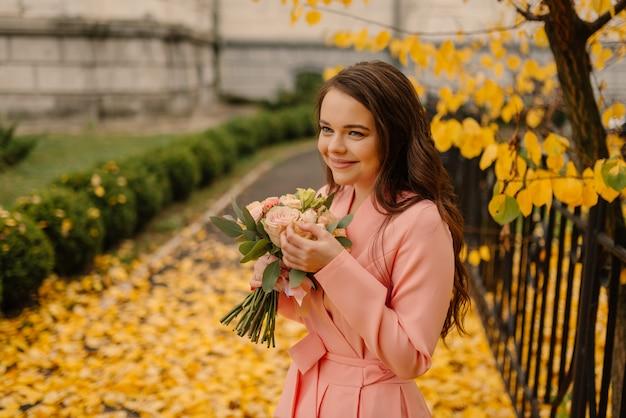 Retrato da noiva morena jovem sensual feliz no vestido de casamento rosa e em pé no parque outono perto da catedral vintage e segurando o buquê de casamento.