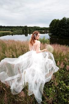 Retrato da noiva vestido de noiva branco com buquê perto do lago, vista traseira