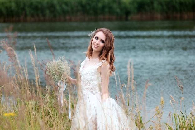 Retrato da noiva vestido de noiva branco com buquê perto do lago
