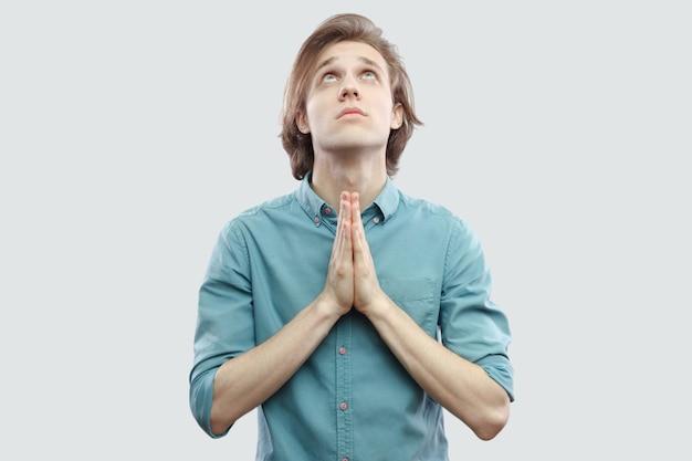 Retrato da palma das mãos jovem loira de cabelos compridos bonito na camisa azul casual em pé olhando para cima e orar ou implorar a deus para perdoá-lo. tiro de estúdio interno, isolado em fundo cinza claro.