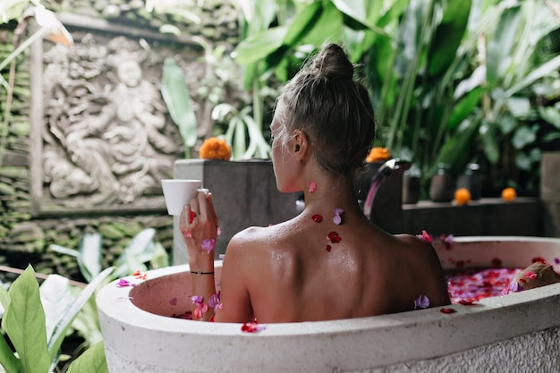 Retrato da parte de trás da graciosa mulher europeia tomando banho com pétalas de rosa e degustação de chá.