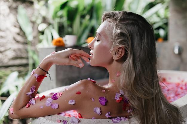 Retrato da parte de trás da mulher caucasiana inspirada, sentada na banheira com pétalas. fascinante jovem relaxando enquanto faz o spa.