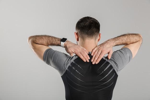 Retrato da parte de trás de um esportista atlético em pé enquanto se exercita, isolado sobre uma parede cinza