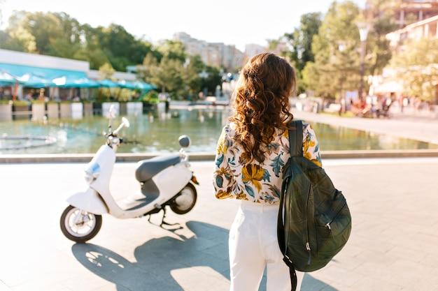 Retrato da parte de trás de uma garota magra com cabelo castanho encaracolado ao lado de uma scooter com uma mochila de couro