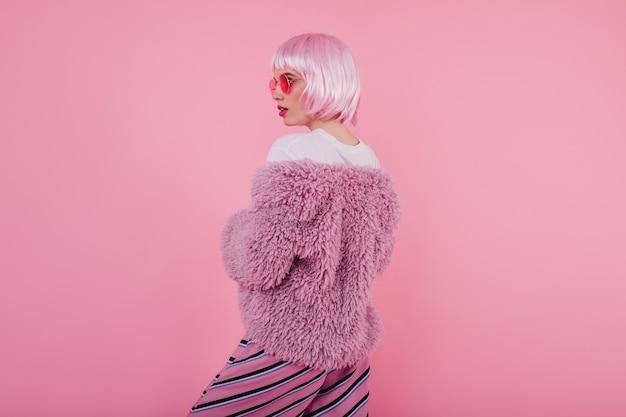 Retrato da parte de trás do gracioso modelo feminino de bom humor, posando com casaco de pele. foto interna da magnífica senhora elegante com óculos escuros e peruca isolada em uma parede pastel