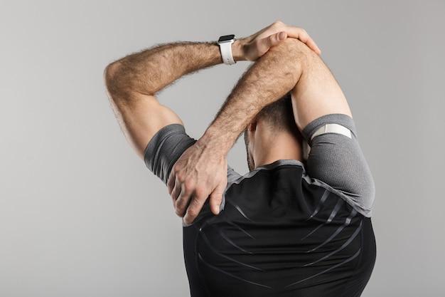 Retrato da parte de trás do homem atlético em roupas esportivas, fazendo exercícios enquanto se exercita, isolado sobre uma parede cinza