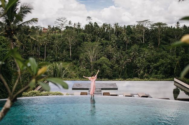 Retrato da parte de trás do modelo feminino em vestido rosa, olhando para a floresta tropical. tiro ao ar livre de mulher graciosa dançando perto da piscina.
