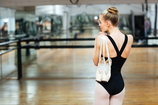 Retrato da parte traseira de uma bailarina de pé e segurando sapatilhas de ponta na aula de balé