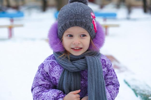Retrato da pequena menina feliz bonito se divertindo na neve em um dia ensolarado de inverno