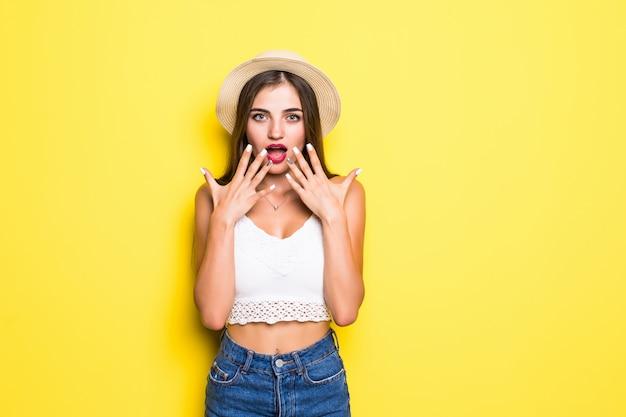 Retrato da posição gritando entusiasmado da jovem mulher isolada sobre a parede amarela.