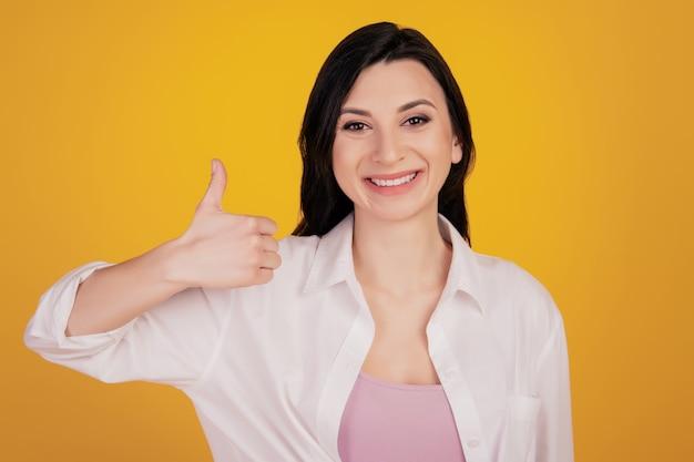 Retrato da promotora levantando o polegar sobre fundo amarelo