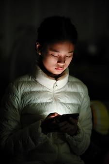 Retrato da rapariga asiática que usa o telefone móvel.