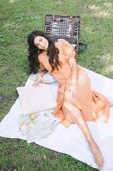 Retrato da senhora bonita na natureza que encontra-se e que olha no vestido alaranjado durante o dia.