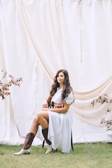 Retrato da senhora bonita no jardim com a parede branca que senta e que sorri no vestido branco longo com a correia durante o dia.