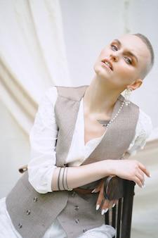 Retrato da senhora bonita que senta e que olha no vestido branco e cinzento durante o dia.