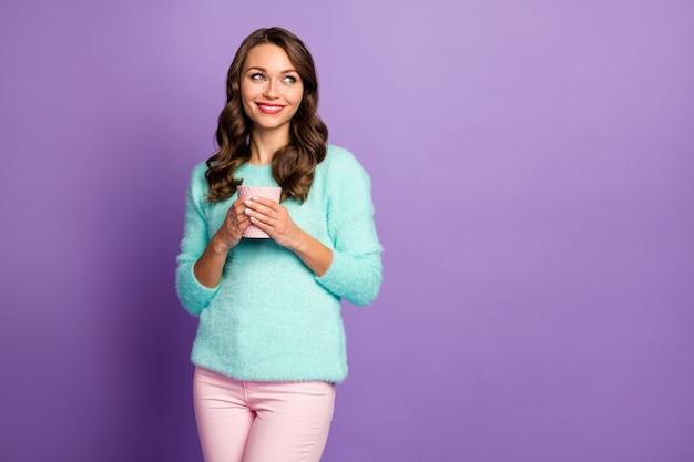 Retrato da senhora bonita sonhadora segurar o copo de bebida de café quente procure o espaço vazio, lembre-se de encontro de amor romântico usar calças rosa suéter difuso pastel.