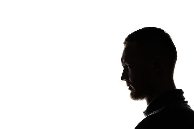 Retrato da visão lateral de um homem, o efeito da luz de fundo, imagem escurecida