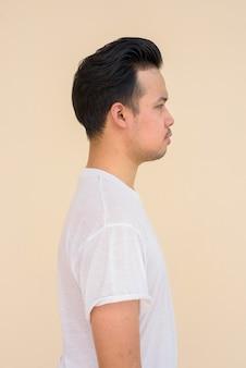 Retrato da vista de perfil de um homem asiático vestindo uma camiseta branca contra um fundo liso ao ar livre