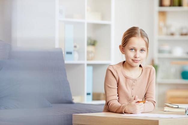 Retrato da vista frontal da linda garota olhando para a câmera enquanto faz a lição de casa ou estuda em casa em um interior aconchegante, copie o espaço