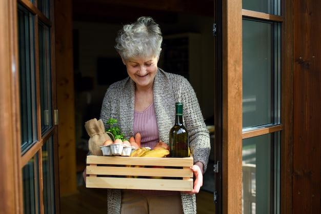 Retrato da vista frontal da mulher segurando a entrega de compras de alimentos pela porta da frente.