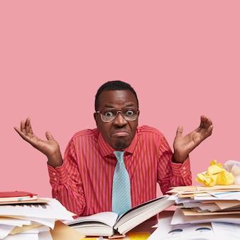 Retrato da vista frontal de um empresário negro confuso com pele escura, aparência engraçada, encolhendo os ombros, imaginando algo