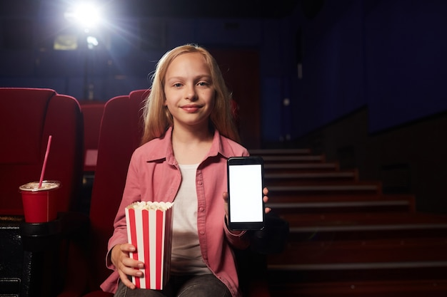 Retrato da vista frontal de uma adolescente loira mostrando smartphone com tela em branco e olhando para a câmera enquanto segura a xícara de pipoca no cinema, copie o espaço