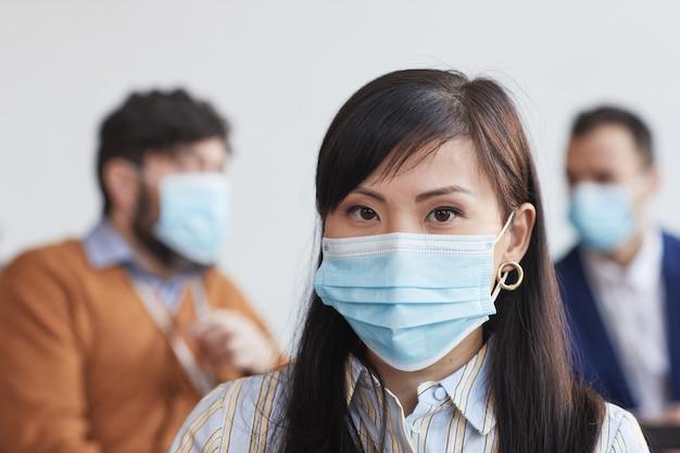 Retrato da vista frontal de uma empresária asiática usando máscara e olhando para a câmera com as pessoas no fundo, copie o espaço