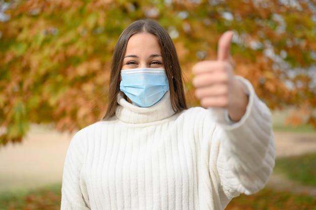 Retrato da vista frontal de uma mulher feliz com máscara protetora apontando o polegar para cima na rua