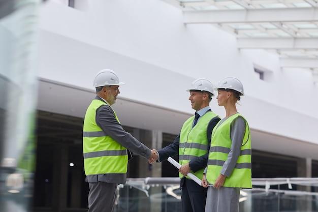 Retrato da vista lateral de executivos sorridentes apertando as mãos após um acordo de investimento no canteiro de obras,
