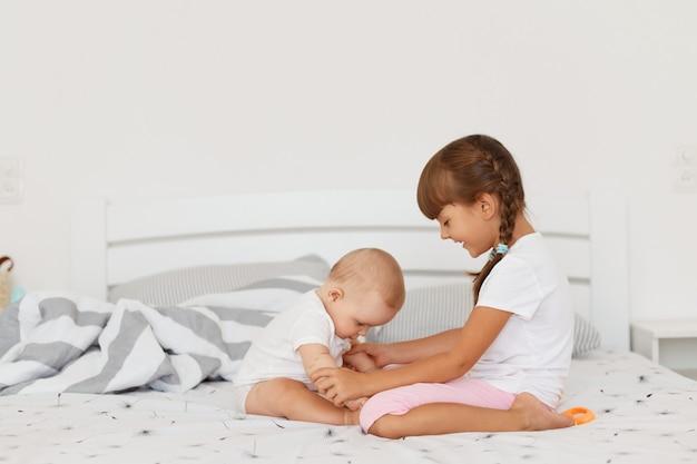 Retrato da vista lateral de lindas garotas felizes sentadas na cama em um quarto claro, crianças vestindo roupas brancas, brincando em casa, passando um tempo juntos, infância feliz.