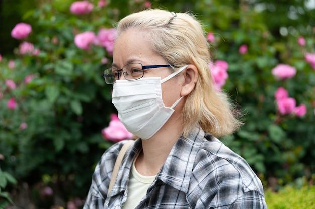 Retrato da vista lateral de mulher loira de raça mista de meia idade com óculos usando máscara cirúrgica branca.
