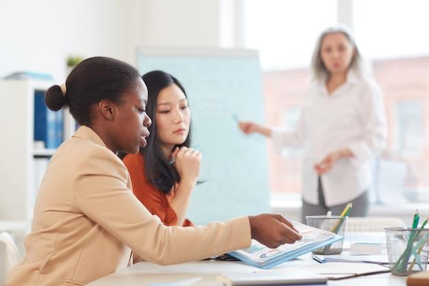 Retrato da vista lateral de mulheres de negócios étnicas modernas planejando projeto enquanto estão sentadas à mesa durante uma reunião na sala de conferências