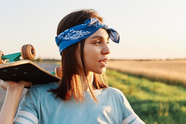 Retrato da vista lateral de pensativa linda mulher vestindo camiseta azul casual e faixa de cabelo elegante, desviando o olhar com olhar pensativo, segurando o skate sobre os ombros.