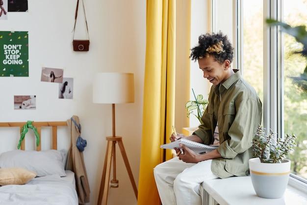 Retrato da vista lateral de um adolescente mestiço sentado na janela em casa escrevendo no caderno, copie o espaço