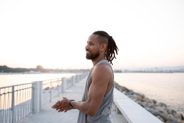 Retrato da vista lateral de um atleta afro-americano fazendo uma pausa