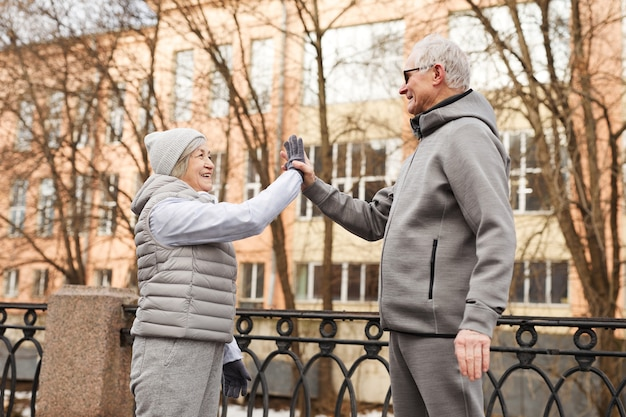 Retrato da vista lateral de um casal de idosos ativos dando alta ao ar livre e sorrindo alegremente